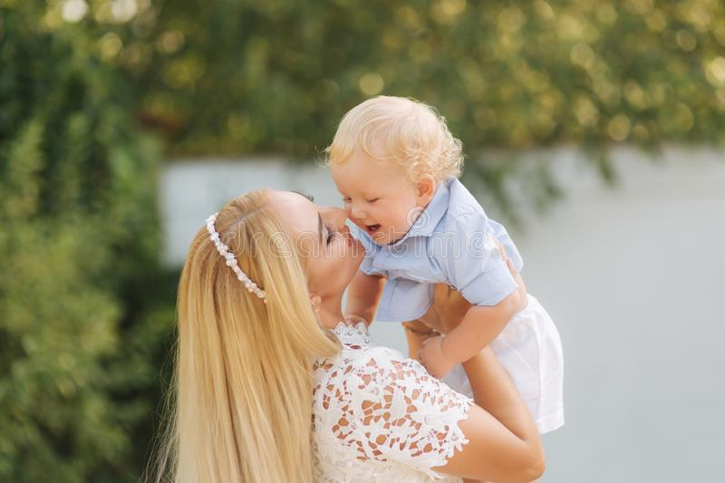 Young blond hair mom play with son outside. Little boy with blond hair. Happy family royalty free stock photo