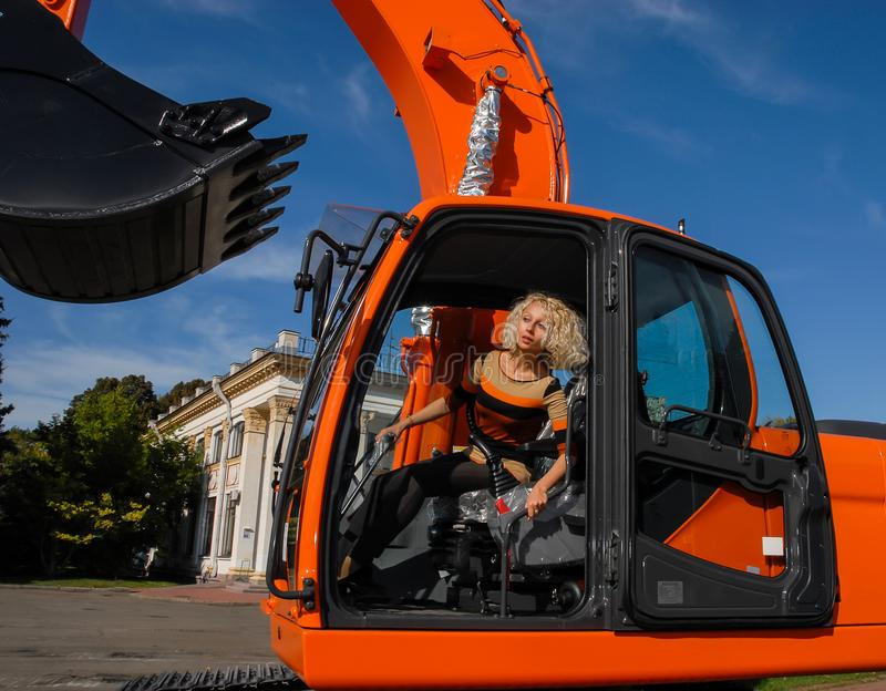 A young blond hair woman sits in a cabin of a new orange crawler excavator with a big black bucket. stock photo