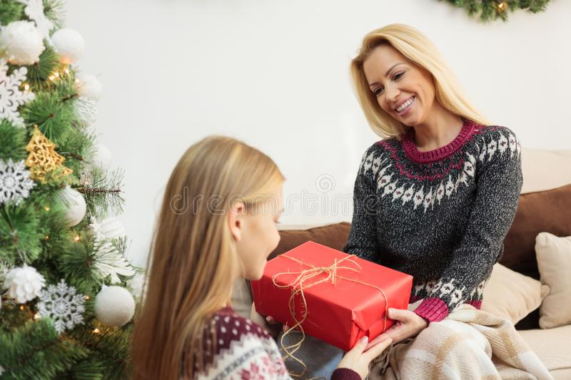 Young blond haired woman giving Christmas gift to her teenage daughter stock photos