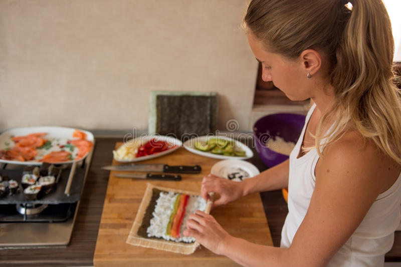 A young, blond haired woman, prepares the Asian dinner in the kitchen stock photography