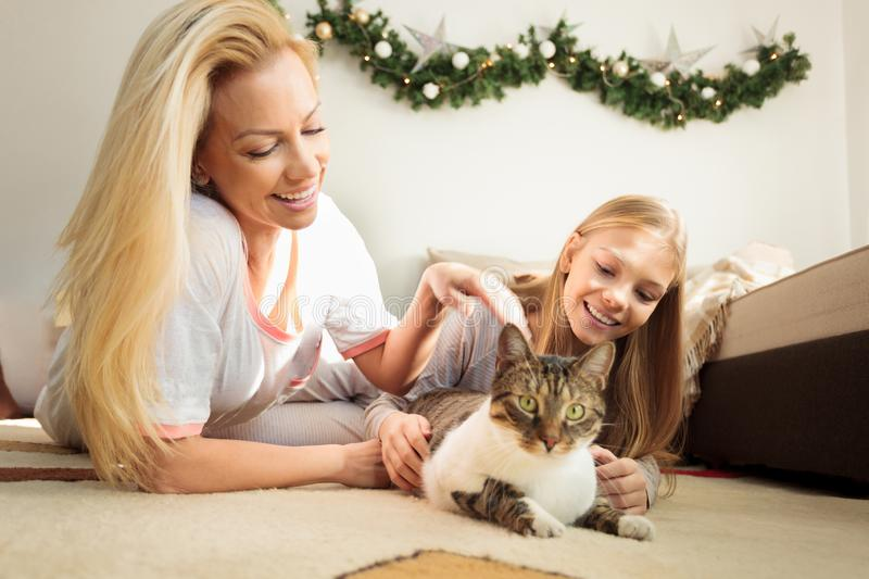 Young blond haired woman and teenage daughter lying on the floor, petting and playing with pet cat. Young blond haired women and teenage daughter lying on the royalty free stock photos