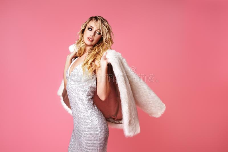 Young Blond Lady in Fashion Dress, Fur Coat. Sexy Woman Posing on Pink Background in Luxury Fashionable Clothes, Shoes stock photo