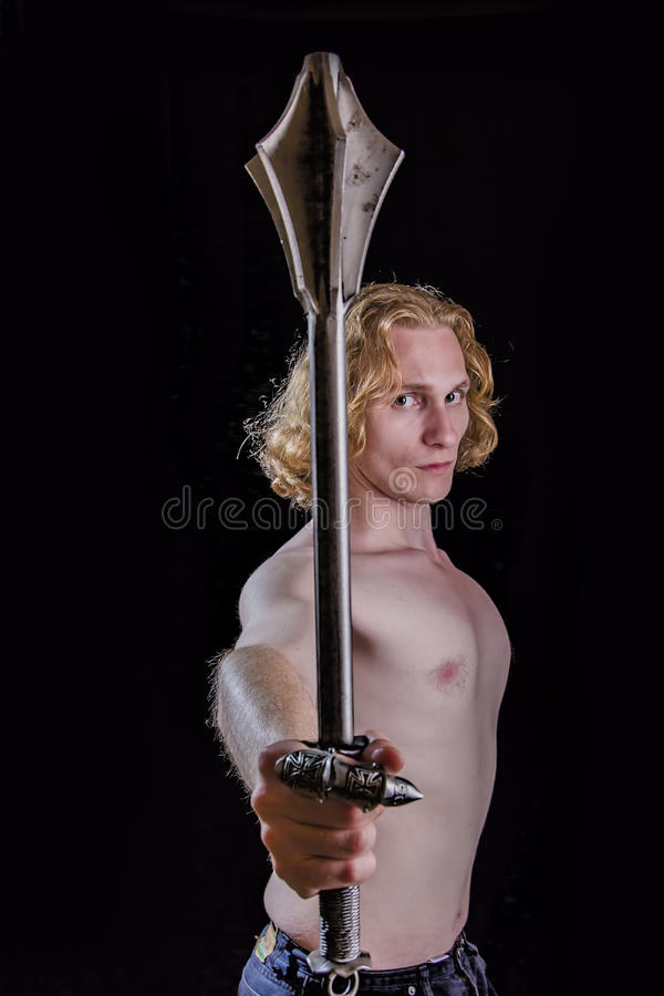 Young blond man holding a medieval weapon royalty free stock photo