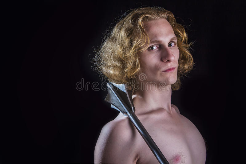 Young blond man holding a medieval weapon stock photos