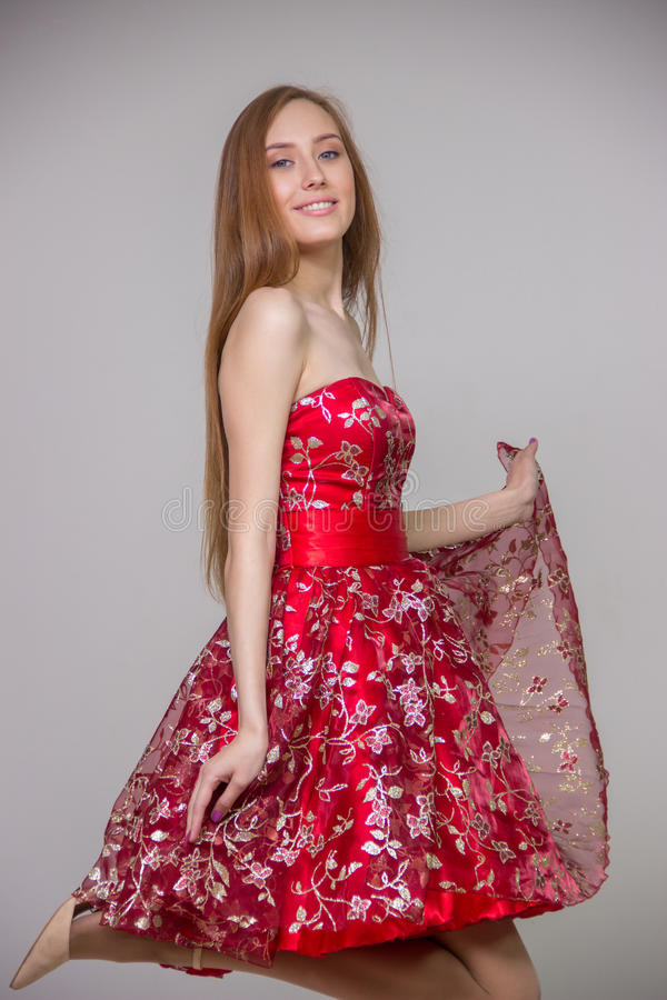 Young blond model with long hair in a smart red dress smiling and having fun on a gray background in the studio stock photography