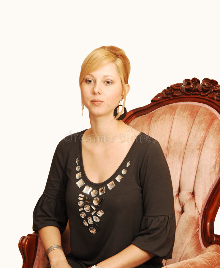 Young blond pretty girl. An blond young lady sitting in an old arm chair in a black top enjoying an relaxing time royalty free stock image