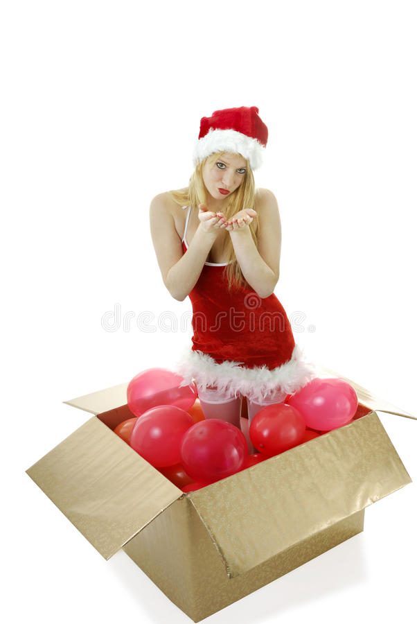 Young Blond Santa Girl In A Box Blowing Kisses Royalty Free Stock Photography