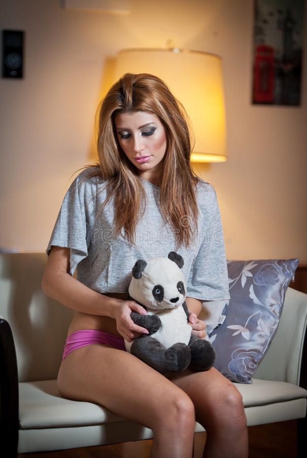 Young blond sensual woman sitting on chair relaxing with a panda bear toy. Beautiful young girl with comfortable clothes relaxing stock photos