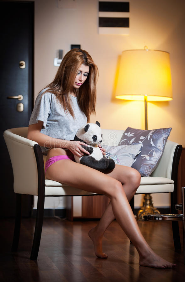 Young blond sensual woman sitting on chair relaxing with a panda bear toy. Beautiful young girl with comfortable clothes relaxing. On the sofa in her room stock images