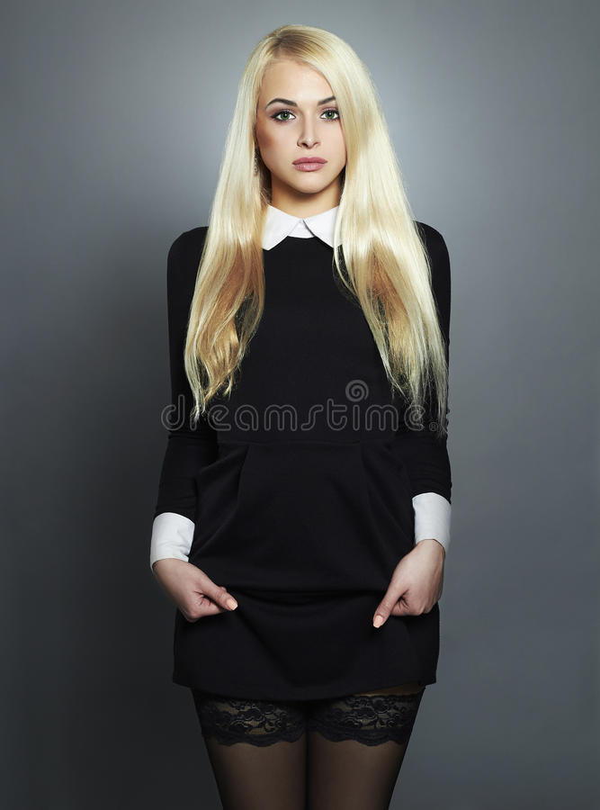 Young blond woman.Beautiful Girl in black dress.schoolgirl royalty free stock photos