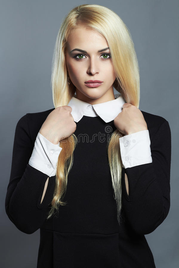 Young blond woman. Beautiful Girl in black schoolgirl dress royalty free stock photos