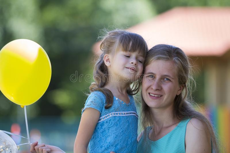 Young blond smiling happily mother hugs lovingly and protectively her small pretty preschool daughter girl with bright balloons o stock image