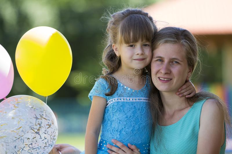 Young blond smiling happily mother hugs lovingly and protectively her small pretty preschool daughter girl with bright balloons on stock images