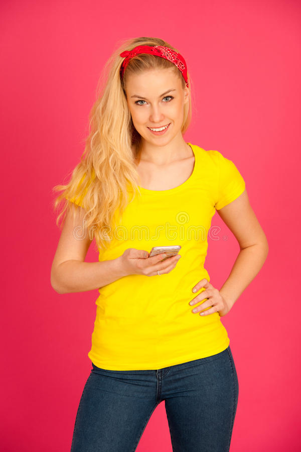 Young blond teenage girl in yellow t shirt surfing the web on sm stock photography