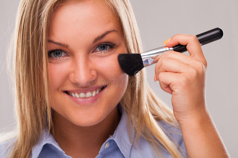 Young blond woman with brush royalty free stock image