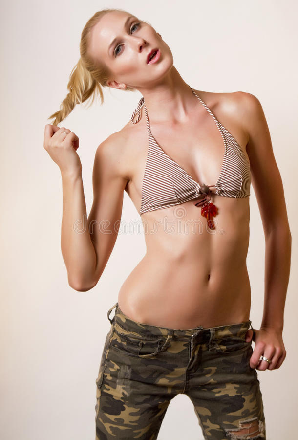 Young blond woman in camouflage stock photography