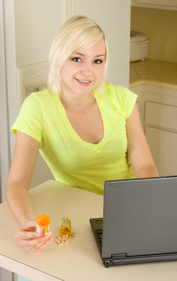 Young blond woman by computer with medicine royalty free stock photography