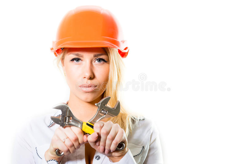 Young blond woman in constructor helmet holding spanner tool royalty free stock images