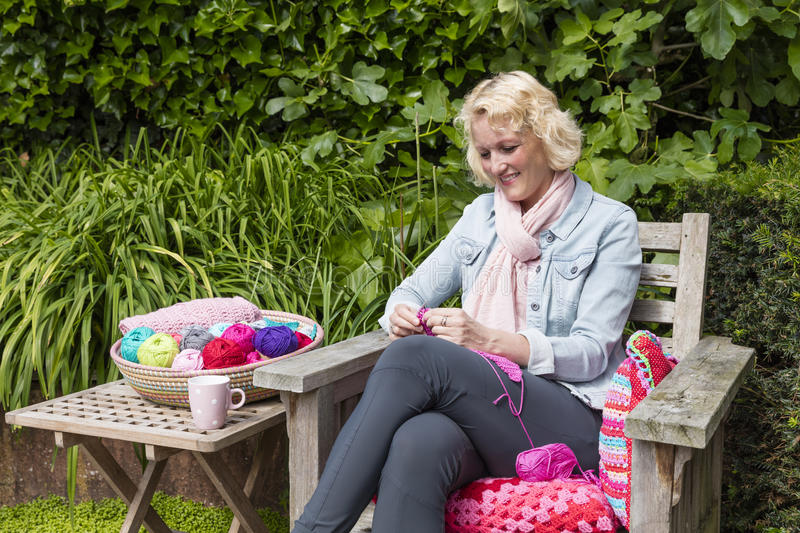 Young Blond Woman Crochets In The Garden royalty free stock image