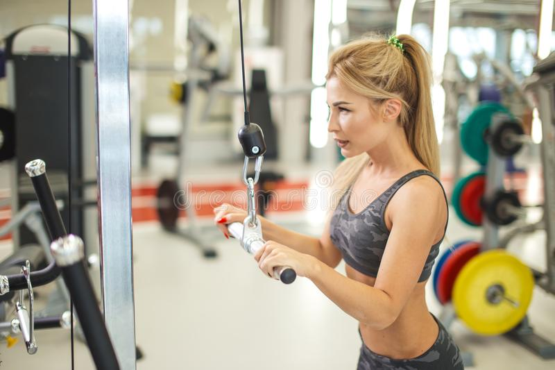 Young blond woman doing exercise for her back in the modern gym. stock images