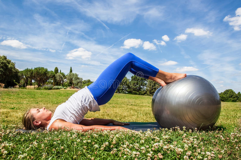 Young blond woman doing fitness, toning up stomach stock photos