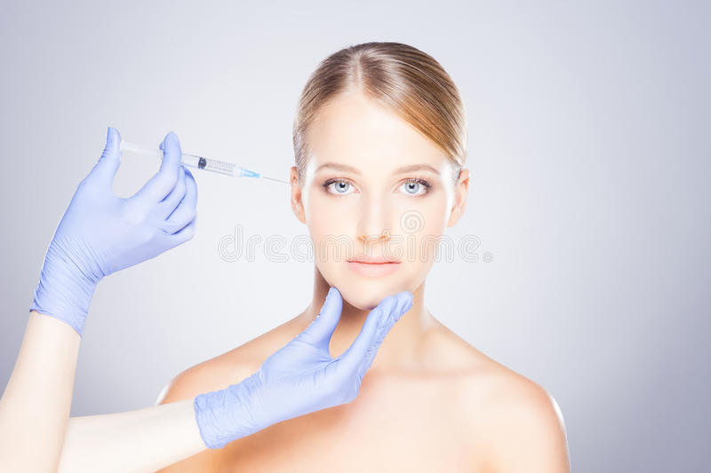 Young blond woman on a face injection procedure stock image