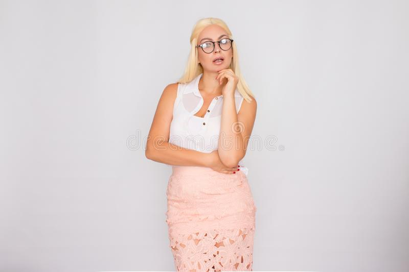 Young blond woman in glasses posing on a white background in the studio royalty free stock photography