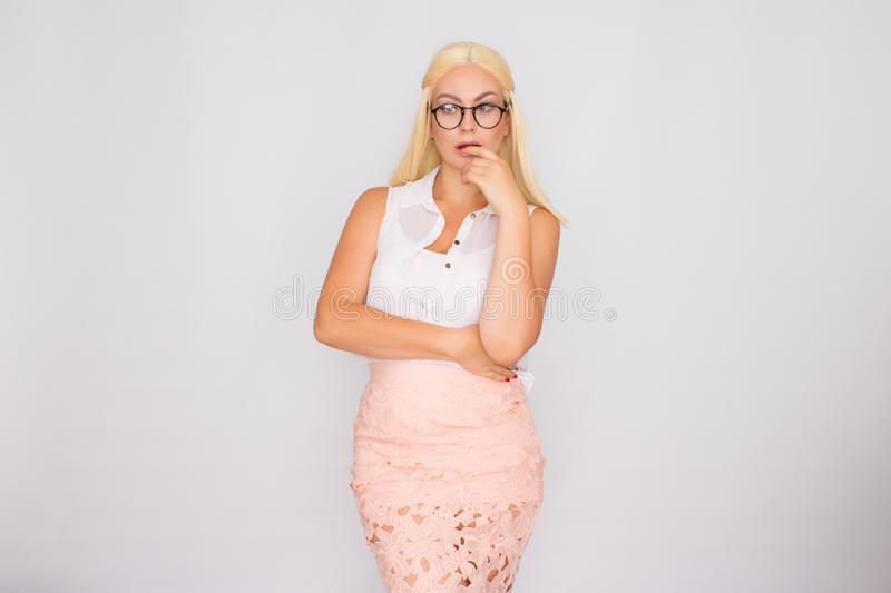 Young blond woman in glasses posing on a white background in the studio royalty free stock photos