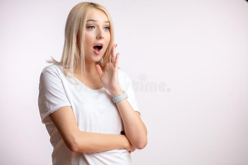 Young blond woman with hand near the face is gossipping stock image