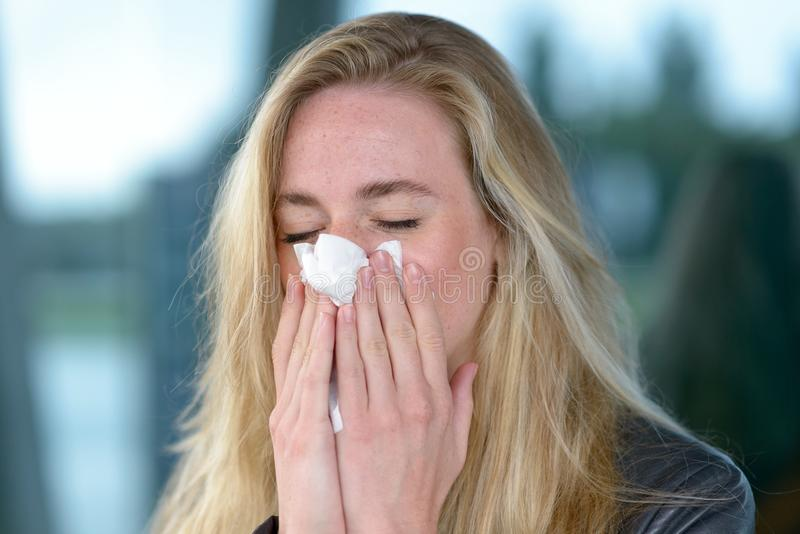 Young blond woman with hay fever stock photography