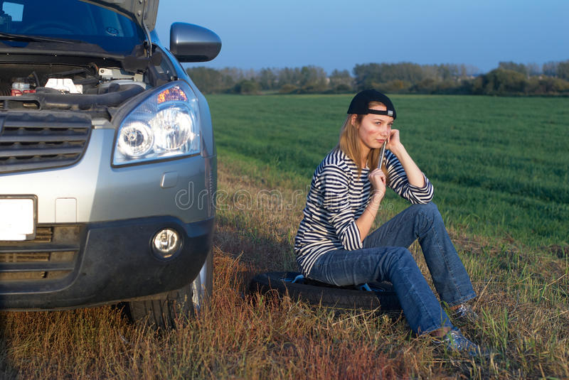 Young Blond Woman With Her Broken Car. The girl is angry royalty free stock photography