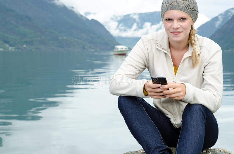 Young Blond Woman With Her Smartphone In The Hand Royalty Free Stock Image