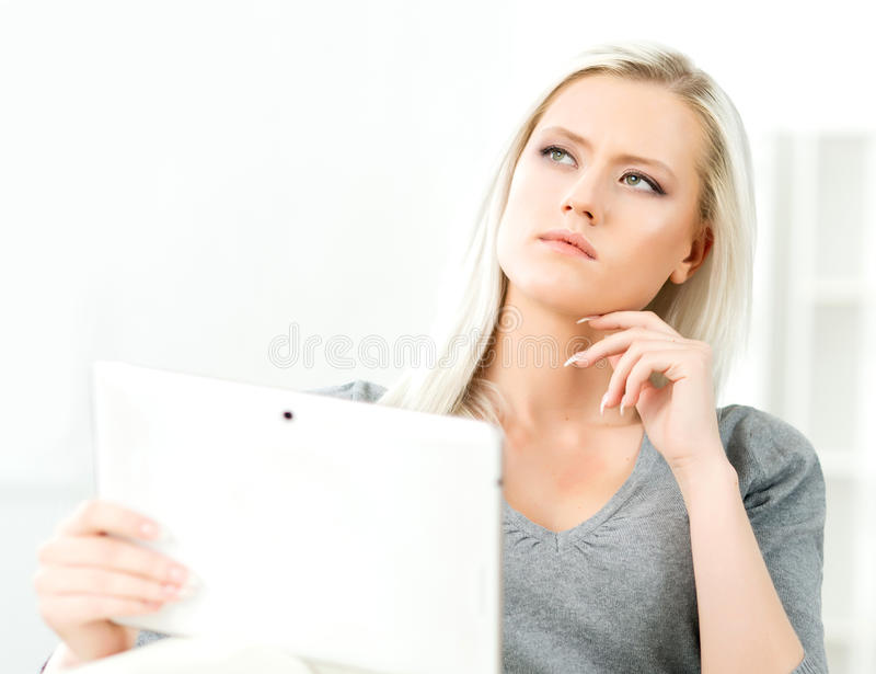Young blond woman holding a tablet. Young and attractive blond woman holding a tablet royalty free stock images