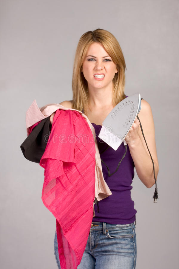 Young blond woman with iron and pile of clothes stock photo