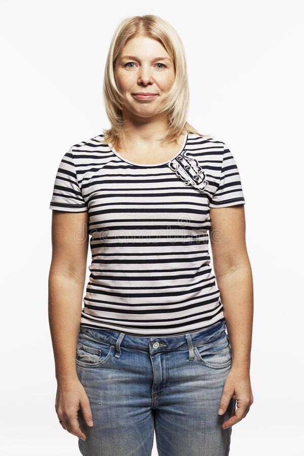 Young blond woman in jeans. White background. Vertical royalty free stock image
