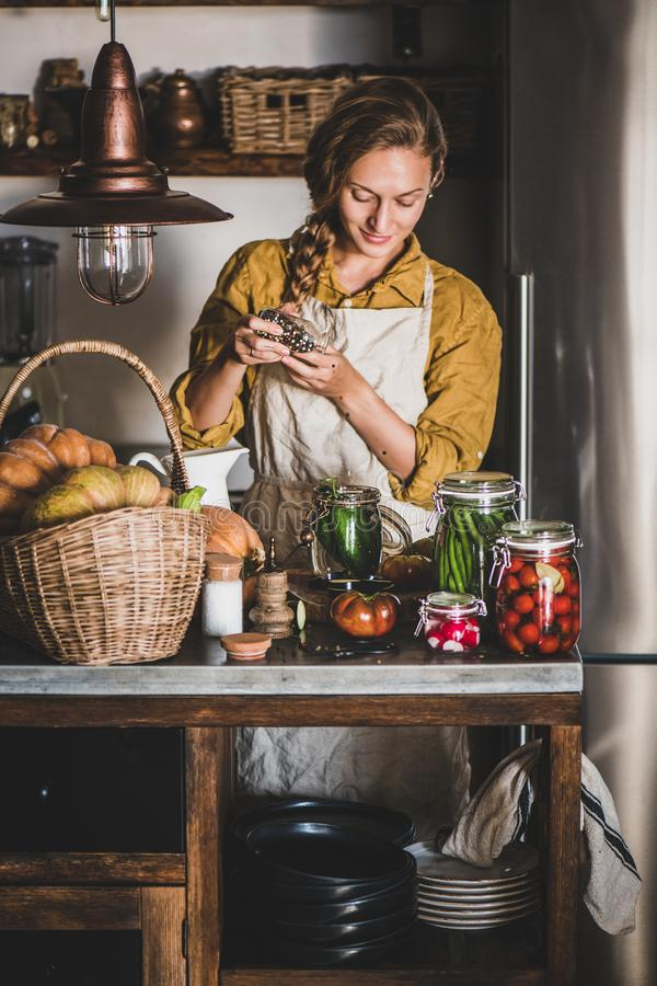 Young blond woman in linen apron cooking homemade vegetable preserves stock photography
