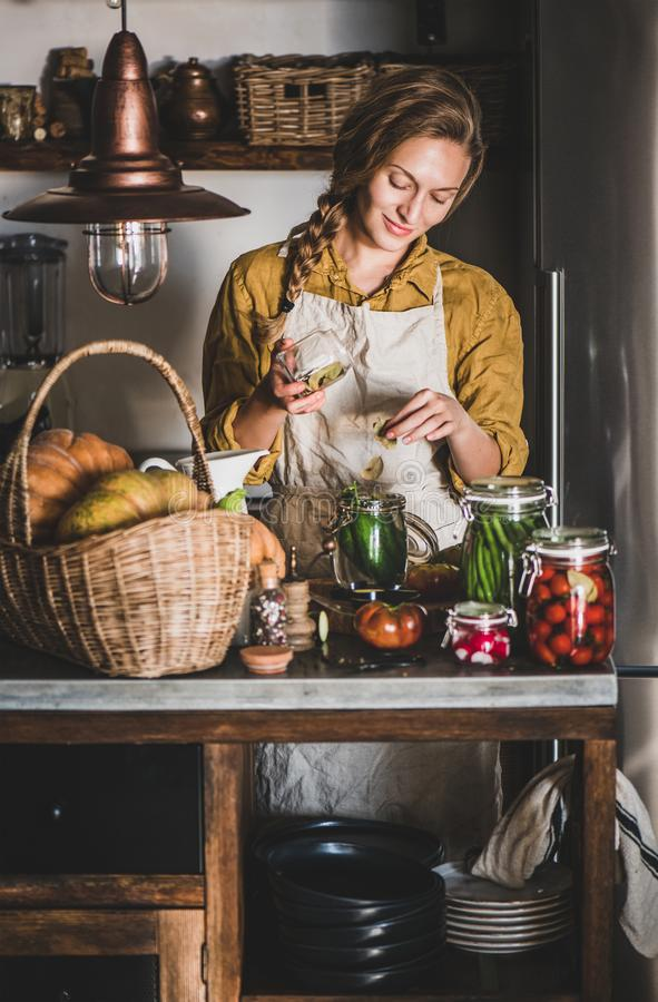 Young blond woman in linen apron making homemade vegetable preserves royalty free stock image