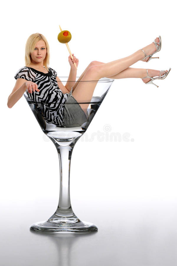 Young Blond Woman in a martini glass. Holding a green olive and isolated on a white background royalty free stock images