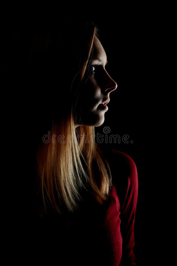 Young blond woman at night in profile royalty free stock photography