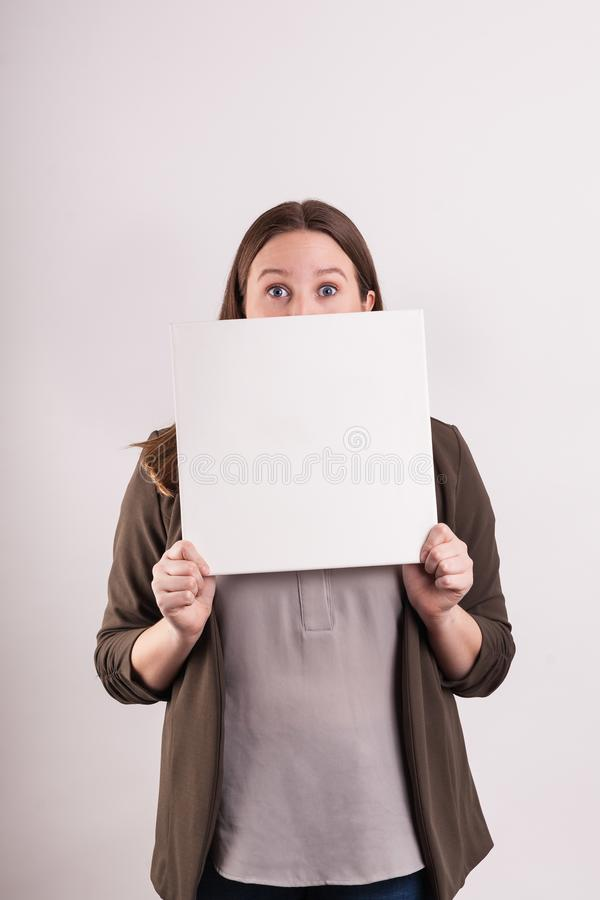 Young female blond peeking over blank massage board on solid background. Young blond woman peeking over a blank white  massage board only eyes showing on solid stock photos