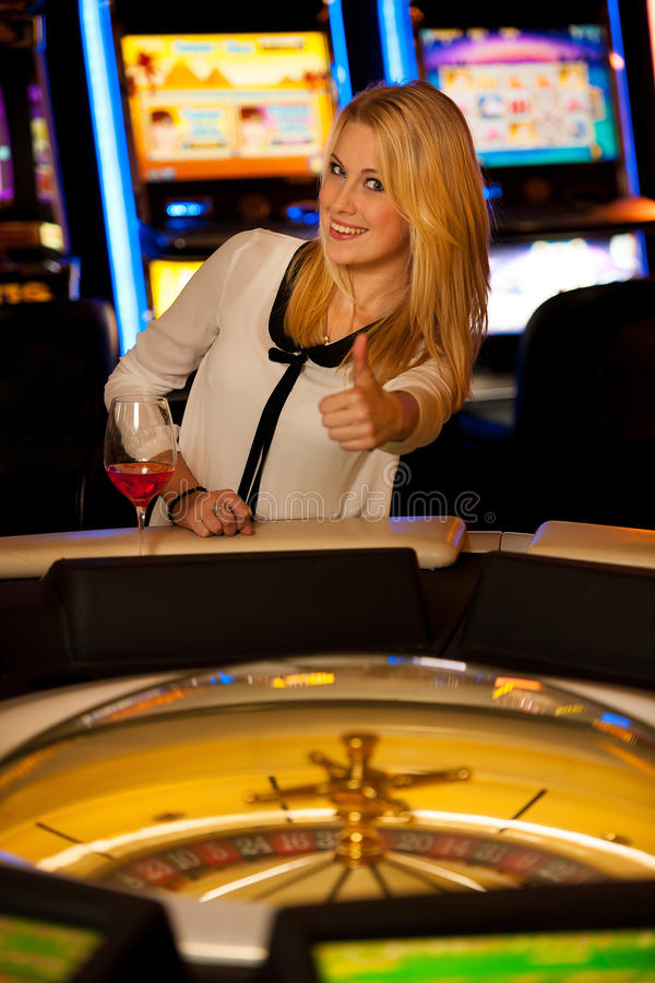 Young blond woman playing roulette in casino and winning. Showing thumb up as a gesture of success stock photos