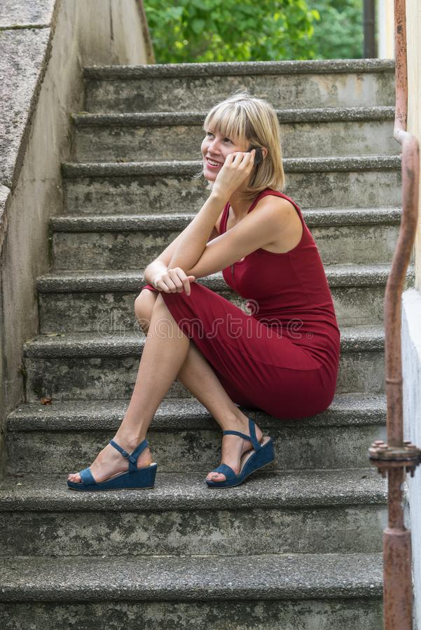 Young blond woman in a red dress siting on the stairs and talking on the cell phone. stock photo