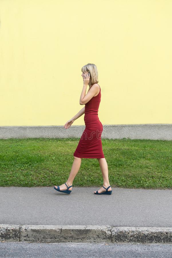 Young blond woman in a red dress walking on the street and talking on the cell phone. stock images