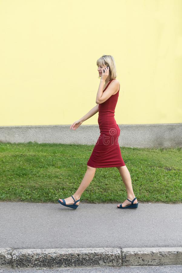 Young blond woman in a red dress walking on the street and talking on the cell phone. royalty free stock image
