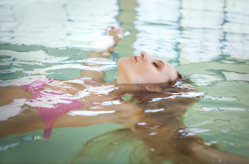 Young blond woman relaxing in the water. In the pool royalty free stock images