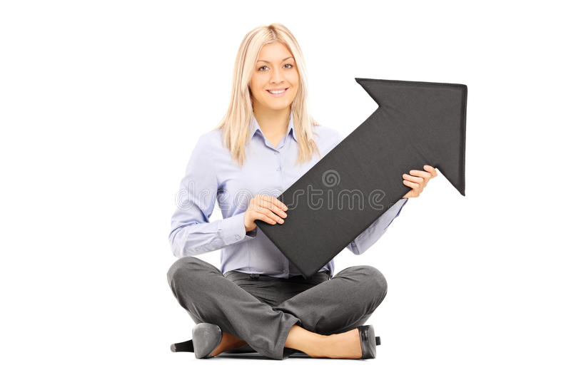 Young blond woman seated on a floor holding a big black arrow royalty free stock image