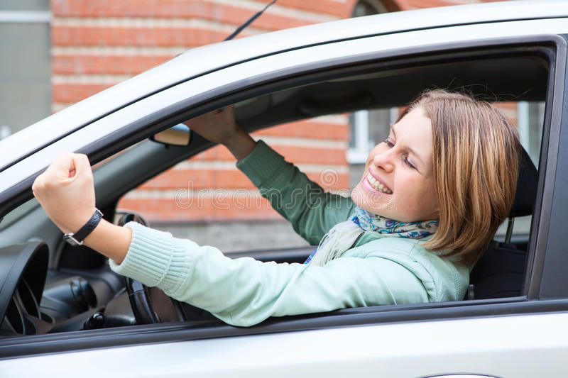 Young blond woman shaking hers fist in car
