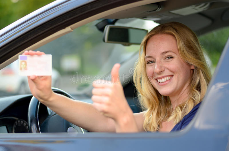 Young blond woman showing off her drivers license. Young blond woman sitting behind the steering wheel of a car showing off her drivers license with a proud royalty free stock image