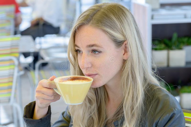 Young blond woman drinking coffee stock images