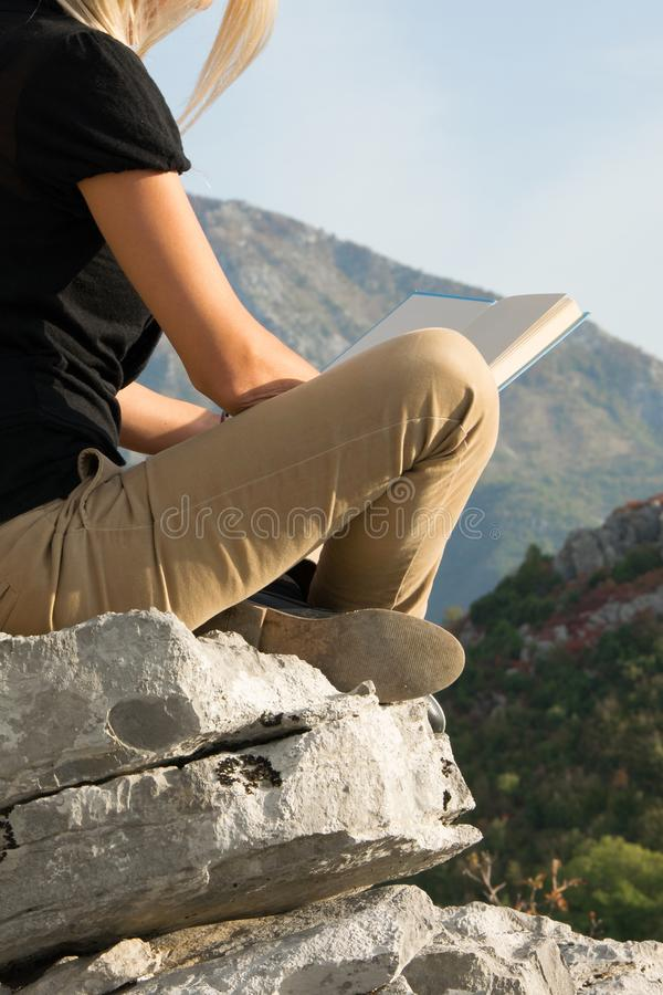 Young blond woman sitting on the edge of the mountain cliff reading a book against beautiful mountains peak stock photos